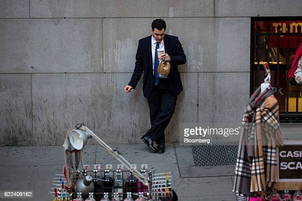A man leans on a wall across from the New York Stock Exchange in New York US on Friday Nov 11 2016 US stocks fluctuated in whipsaw trading with the...