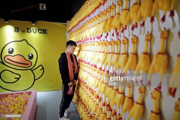 A man leans on a wall full of Screaming Chicken at a stressrelief museum on November 18 2019 in Suzhou Jiangsu Province of China