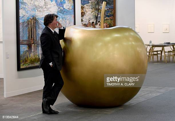 A man leans on 'Pomme dHiver' by Claude Lalanne during the VIP opening of The Armory Show 2016 in New York March 2 2016 / AFP / Timothy A CLARY /...