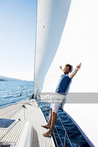 Man leans on sail at bow of yacht