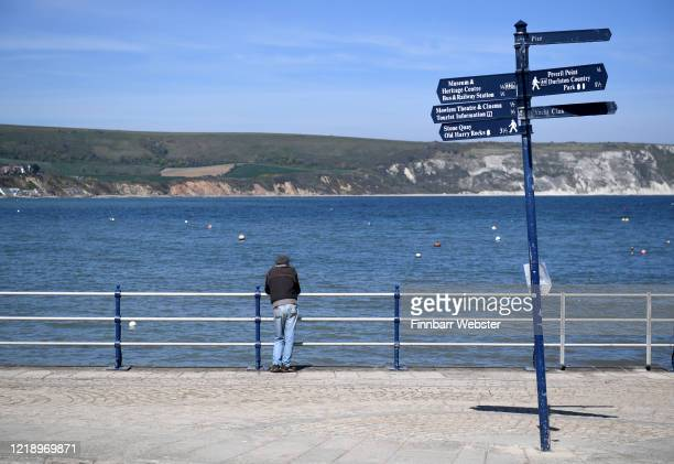 Man leans on the railings on the seafront on April 15, 2020 in Swanage, United Kingdom. The Coronavirus pandemic has spread to many countries across...