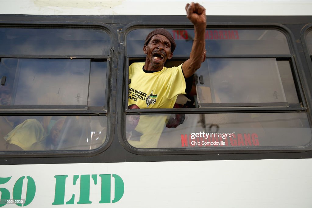 A man leans out of a bus to cheer on demonstrators as they block roads, protesting their inability to see the body of former South African president Nelson Mandela December 14, 2013 in Mthatha, South Africa. Many people in the Eastern Cape are upset about not being able to see Mandela's body. Mandela's body will remain in his home town of Qunu, Eastern Cape, overnight and be buried Sunday. Mr. Mandela passed away on the evening of December 5, 2013 at his home in Houghton at the age of 95. Mandela became South Africa's first black president in 1994 after spending 27 years in jail for his activism against apartheid in a racially-divided South Africa.