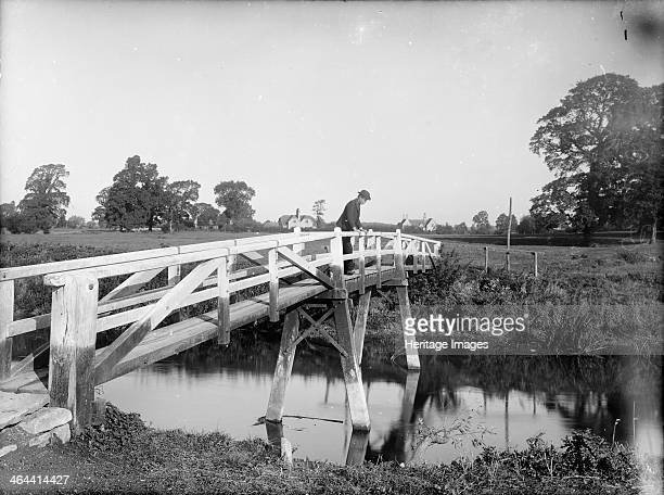 A man leans over the Eisey Footbridge Cricklade Wiltshire and looks into the River Thames c1860c1922
