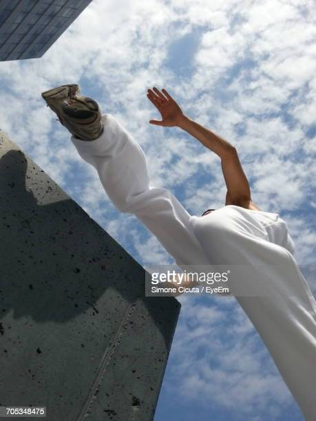 Man Leaping Between Concrete Plinth As Viewed From Underneath