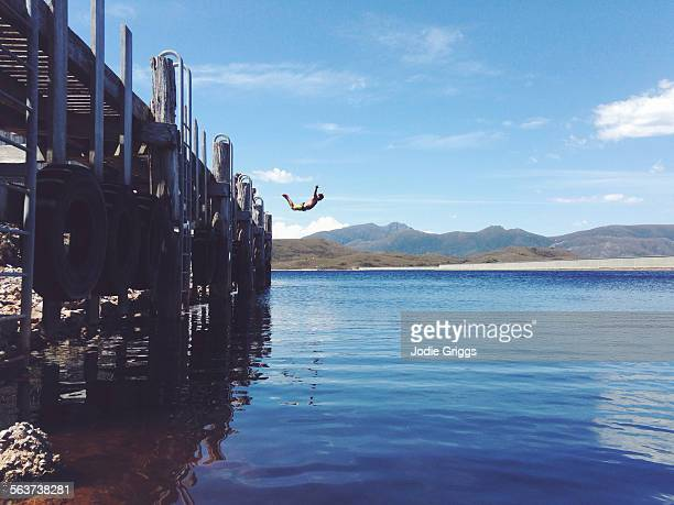 Man leaping from a jetty into a lake