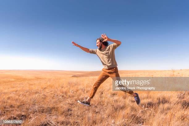 man leaping in field - calça comprida - fotografias e filmes do acervo