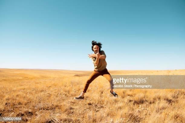 man leaping in field - チノパンツ ストックフォトと画像