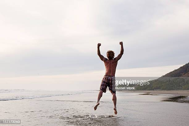 Man leaping in the air at the beach