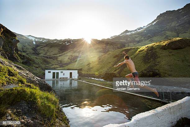 A man leaping into a hot spring.