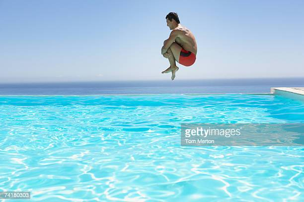 man leaping into infinity pool - pool stock pictures, royalty-free photos & images
