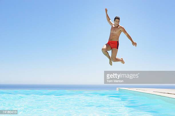man leaping into infinity pool - zwembroek stockfoto's en -beelden