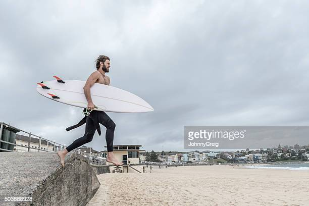 Man leaping off wall with surfboard, Bondi Beach