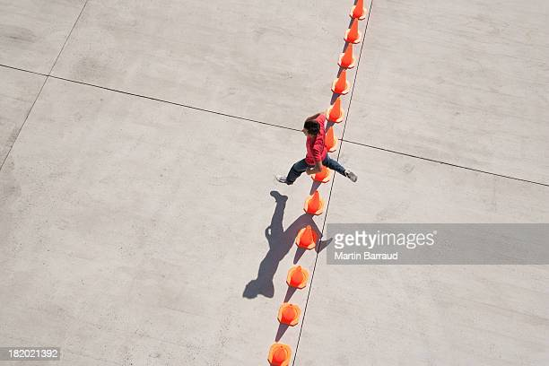 mann, springen über reihe von verkehr kegel - wurf oder sprungdisziplin herren stock-fotos und bilder