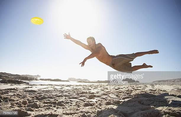 A man leaping through the air at the beach