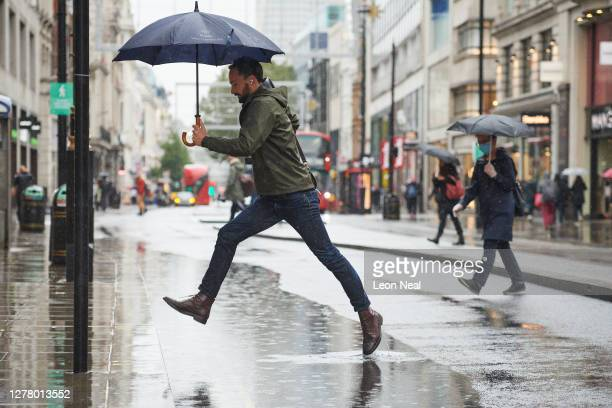 Man leaps over a puddle on Oxford Street following heavy rain on October 02, 2020 in London, England.