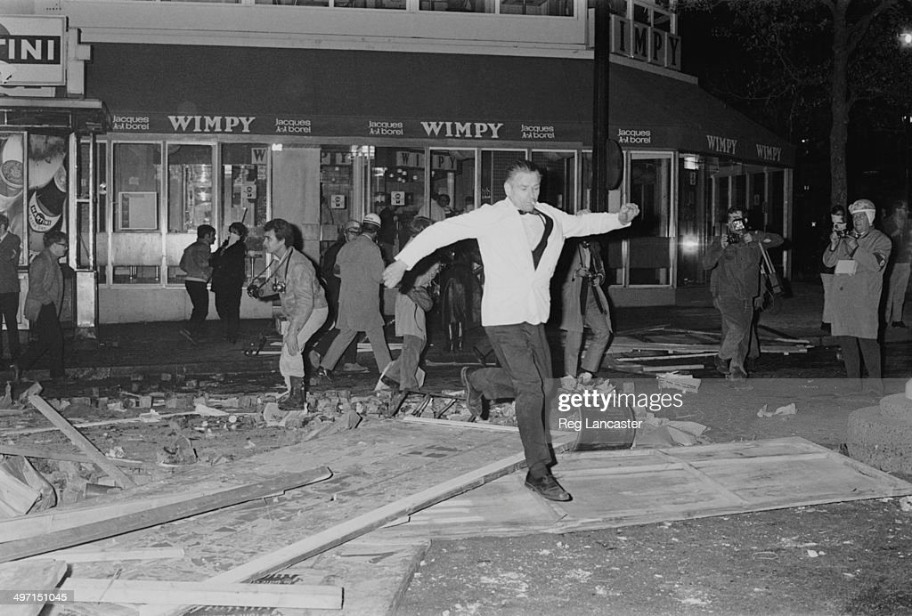 A man leaps over debris in the street during rioting near the Sorbonne in Paris, 12th June 1968. Among the people behind him are four photographers.