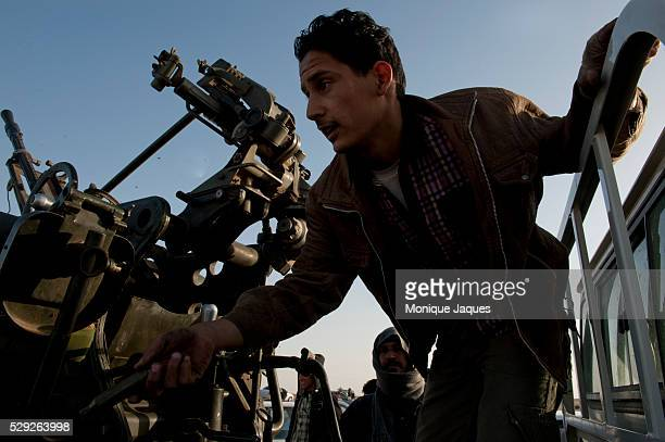 A man learns how to use an AntiAircraft gun outside of a checkpoint in Brega LIbya Rebel troops are largely made out of Volunteers lack knowladge of...