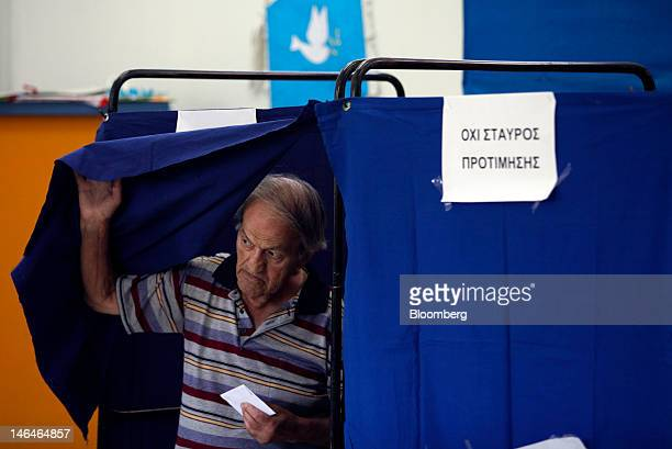 A man leaves a booth after marking his ballot paper ahead of voting in the second round of the Greek general elections at a polling station in Athens...