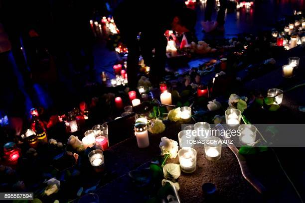 A man leaves a candle at the memorial shift for the victims of the 2016 deadly truck attack at the Christmas market at Breitscheidplatz in front of...