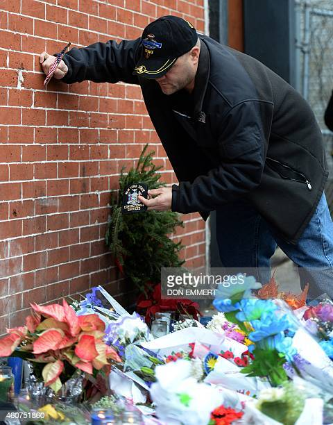 A man leaves a correctional services patch at a memorial near Tompkins Ave and Myrtle Ave December 21 2014 in New York near the site where two New...