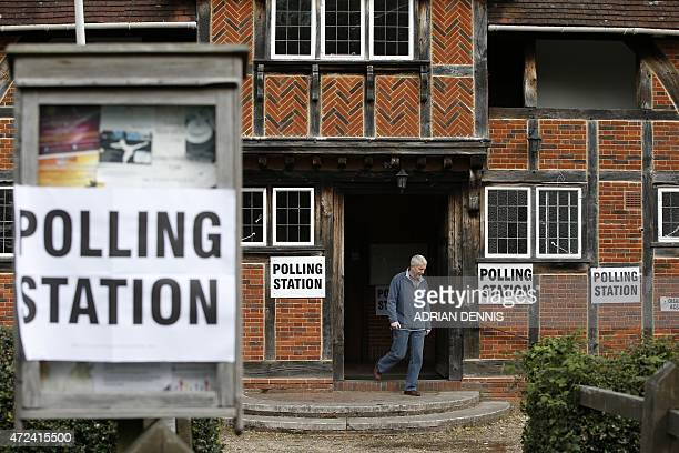 A man leaves a polling station in Rotherwick southern England after voting on May 7 as Britain holds a general election Polls opened today in...