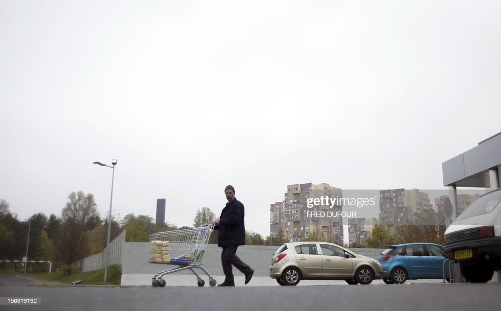 A man leaves a supermarket in Sevran, outside Paris, on November 13, 2012. Ecologist mayor of Sevran Stephane Gatignon is on hunger strike in front of the national Assembly in Paris to make a 'distress call' in order to increase the budget allocated to the 100 poorest cities.