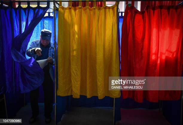 TOPSHOT A man leaves a vote cabin at a polling station in Bucharest October 7 in a referendum to change the constitutional definition of 'family'...