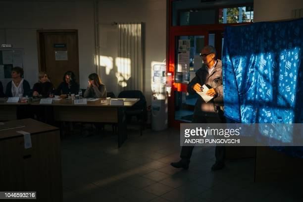 A man leaves a voting booth after casting his vote in Magurele Romania on October 6 2018 Romanians are expected to go to the polls on Saturday and...