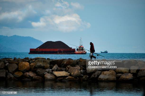 A man leaves after fishing as a tugboat pulling a barge filled with coal is seen along the coast of Banda Aceh on April 26 2020