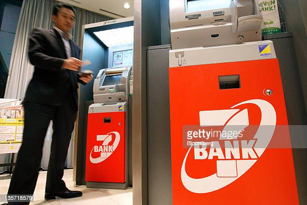 A man leaves after using an automated teller machine at a Seven Bank Ltd branch in Tokyo Japan on Tuesday Dec 13 2011 Shareholders in Seven Bank Ltd...
