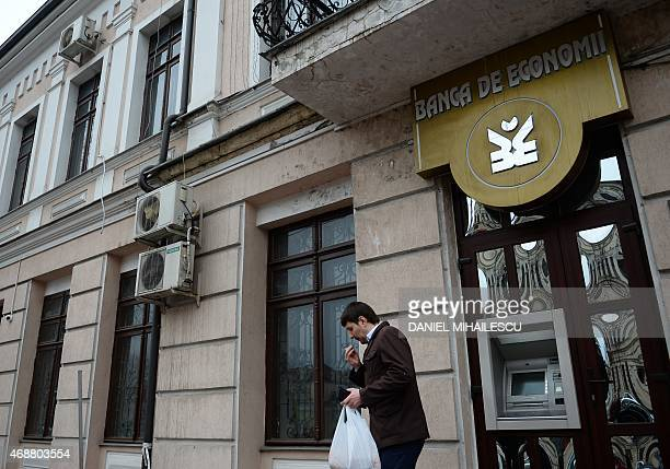 Man leaves an automatic teller machine of Banca de Economii in Chisinau on March 27, 2015. A billion dollars is a lot for Europe's poorest state of...