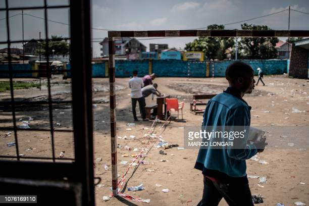 A man leaves as witnesses at a polling station in Kinshasa sign a printout of a electronic voting machine results on December 31 2018 a day after the...