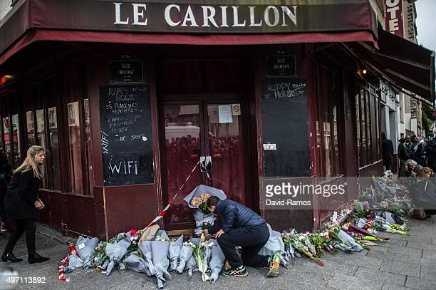 A man leaves floral tributes at the main entrance of Le Carillon restaurant on November 14 2015 in Paris France At least 120 people have been killed...