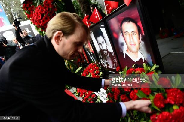A man leaves flowers next to portraits of victims in front of the Reina nightclub in Istanbul on December 31 a year after an attack on the club that...