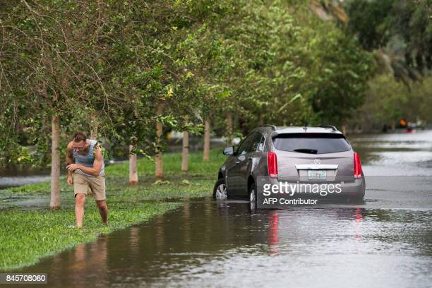 A man leaves his disabled vehicle on the flooded streets of the San Marco historic district of Jacksonville Florida on September 11 after storm surge...