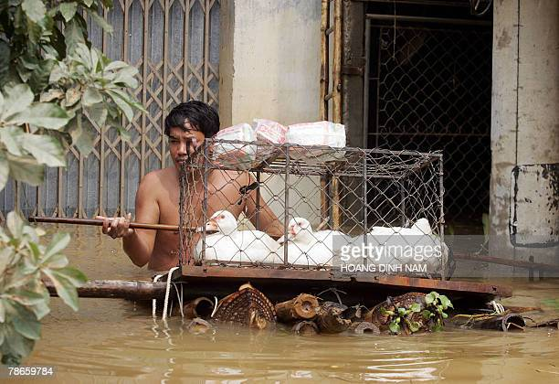 A man leaves his flooded house with a cage of ducks in the Thach Thanh district in the central province of Thanh Hoa 08 October 2007 Some 58 people...