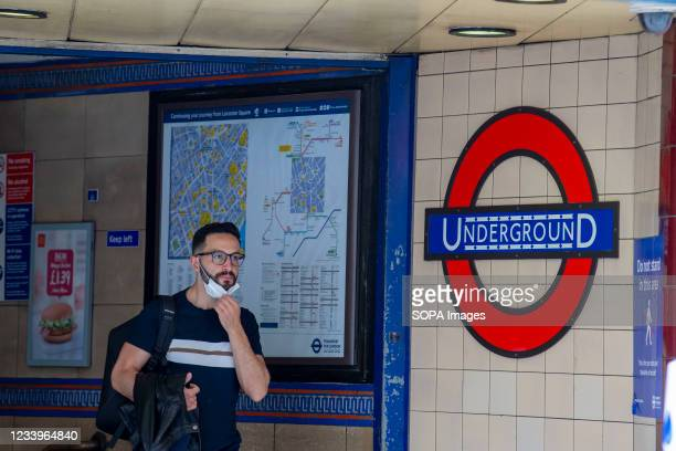 Man leaves Leicester Square underground station wearing a face mask. The mandatory wearing of Face masks on public transport in England is to end on...