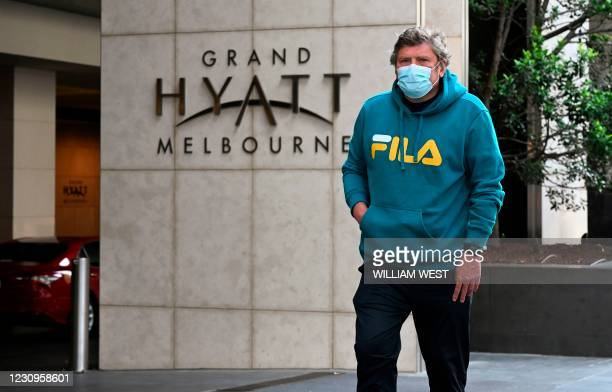 Man leaves the Grand Hyatt hotel in Melbourne on February 4 as preparations for the Australian Open were thrown into chaos when up to 600 players and...