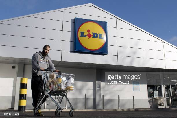 Man leaves with his goods after shopping at a branch of Lidl supermarket in south London, on January 10, 2018. - Traditional supermarket chains, such...
