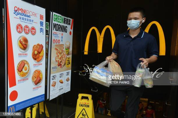 Man leaves with takeaway food past signs advertising new plant-based vegan-friendly meatless dishes at a McDonald's fastfood restaurant in Hong Kong...