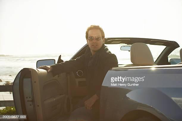 man leaving convertible car by beach - 降り立つ ストックフォトと画像