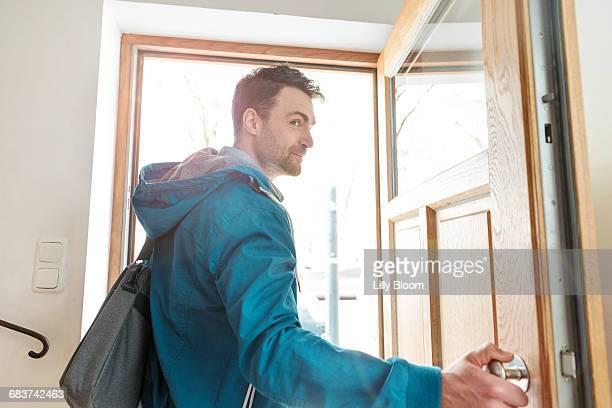 Man leaving front door of house