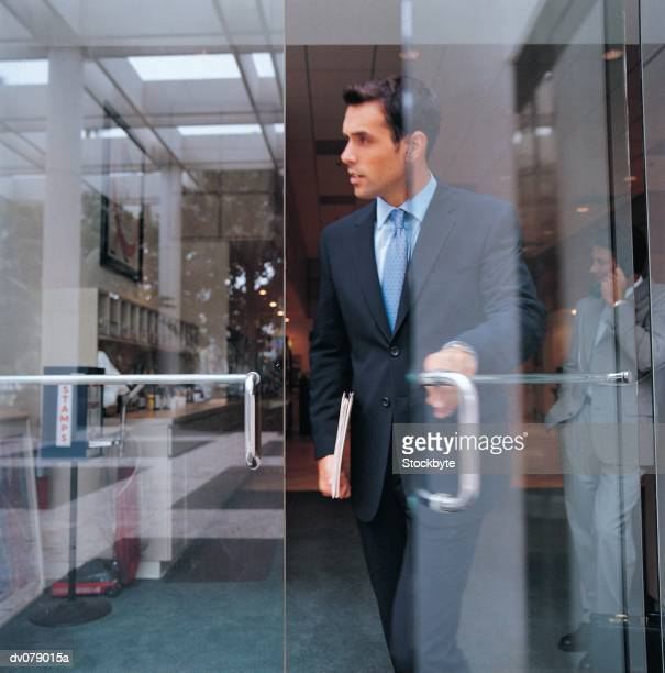 Man leaving office building; second man in background talking on cellular phone