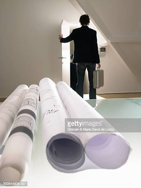 Man leaving office, rolled up blueprints in foreground