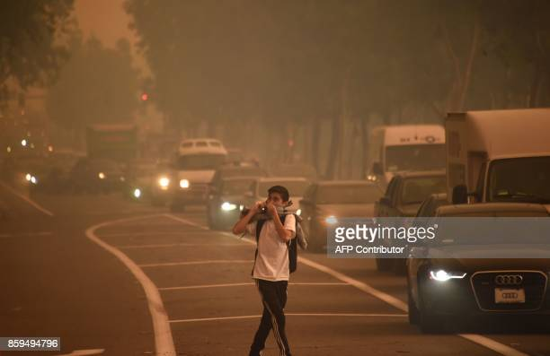 A man leaving Santiago Canyon College in Orange California looks back as strong Santa Ana winds blow fire and smoke toward the college on October 9as...