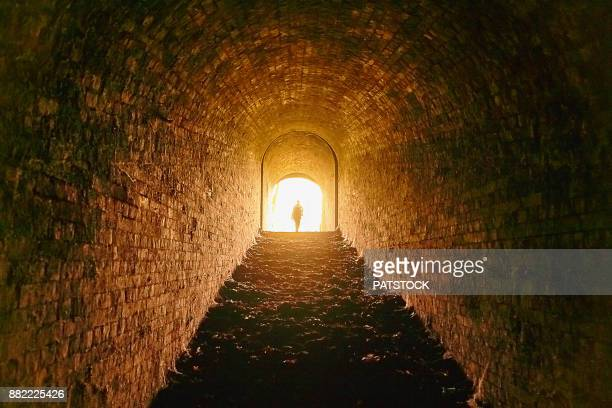 man leaving tunnel - escaping stock pictures, royalty-free photos & images