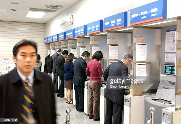 A man left walks out of a Mizuho Bank branch in downtown Tokyo while other customers use ATMs on Monday December 20 2004 Mizuho Financial Group Inc...