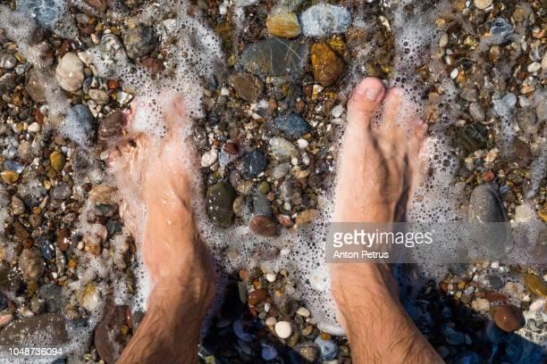Man legs on the pebble beach