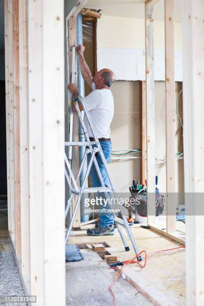 man levelling beam during home renovations - powerofforever stock pictures, royalty-free photos & images