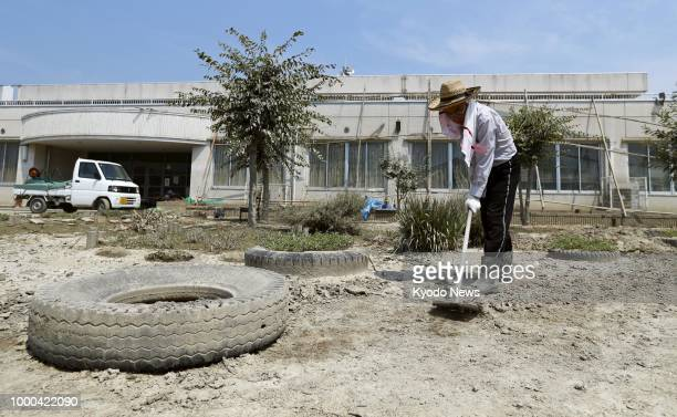 A man levels the ground of Yata Elementary School in Kurashiki Okayama Prefecture after it had been damaged by floods caused by torrential rains that...